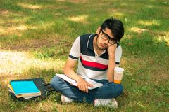 Young cute guy got tired sitting on the grass Royalty Free Stock Photo