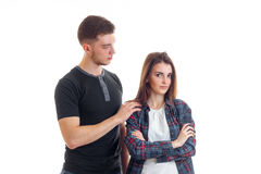 Young cute guy holds arm shoulder serious girl who stands upright hands. Isolated on white background Royalty Free Stock Photography