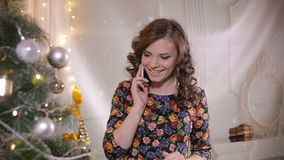 Young cute handsome girl speaks by mobile phone near the Christmas tree. Christmas celebration. stock video footage