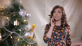 Young cute handsome girl speaks by mobile phone near the Christmas tree. Christmas celebration. stock footage