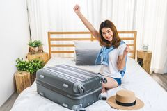 Young cute happy Asian girl finished packing suitcase luggage on bed in bedroom, ready to go abroad solo trip. Asia traveler, Asian tourism, or excited tourist royalty free stock image