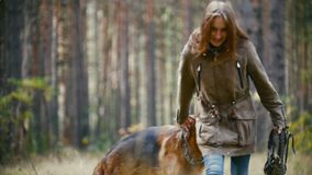 Young cute happy woman plays with her dog - german shepherd in yellow autumn park, slow-motion stock video footage