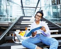 Young cute indian girl at university building sitting on stairs. Reading a book, wearing hipster glasses, lifestyle people concept close up stock images