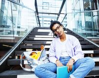 Young cute indian girl at university building sitting on stairs. Reading a book, wearing hipster glasses, lifestyle people concept close up royalty free stock images