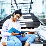 Young cute indian girl at university building sitting on stairs. Reading a book, wearing hipster glasses, lifestyle people concept close up royalty free stock photo