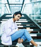 Young cute indian girl at university building sitting on stairs reading a book, wearing hipster glasses, lifestyle. People concept close up stock photo