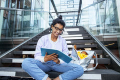 Young cute indian girl at university building sitting on stairs reading a book, wearing hipster glasses, lifestyle. People concept close up stock photos