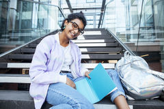 Young cute indian girl at university building sitting on stairs reading a book, wearing hipster glasses, lifestyle. People concept close up royalty free stock photography