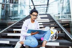 Young cute indian girl at university building sitting on stairs reading a book, wearing hipster glasses, lifestyle. People concept close up stock image