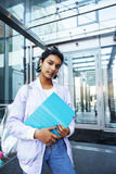 Young cute indian girl at university building sitting on stairs. Reading a book, wearing hipster glasses, lifestyle people concept close up stock photography
