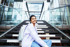 Young cute indian girl at university building sitting on stairs. Reading a book, wearing hipster glasses, lifestyle people concept close up stock image
