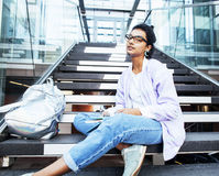 Young cute indian girl at university building sitting on stairs. Reading a book, wearing hipster glasses, lifestyle people concept close up royalty free stock image