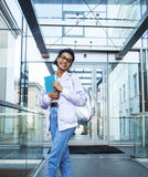 Young cute indian girl at university building sitting on stairs. Reading a book, wearing hipster glasses, lifestyle people concept close up royalty free stock photos