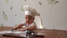 Young cute kid in chef`s cap sits at the wooden table and tastes flour stock footage
