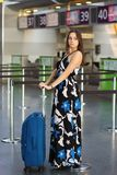 Young cute lady posing at the airport. Standing next to a suitcase dressed in a long dress royalty free stock photo