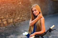 Young cute lady posing with bike near the wall Stock Photos