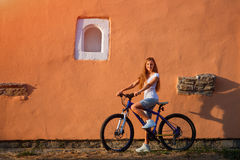 Young cute lady posing on a bike near the wall Royalty Free Stock Image