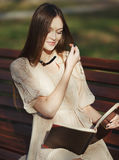 Young cute lady sitting on bench Stock Photography