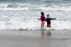 Young cute little boy and girl playing at the seaside running into the surf on a sandy beach in summer sunshine Stock Photography