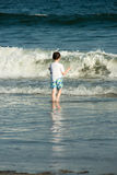Young cute little boy playing at the seaside running into the surf on a sandy beach in summer sunshine Stock Photos