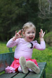 Young cute little girl crazy funny expression on the bank Stock Image