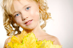 Young cute little girl with orange autumn leaves Stock Photography