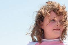 Young cute little girl playing at the seaside running into the surf on a sandy beach in summer sunshine Stock Image