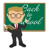 Young cute little primary schoolboy with textbook standing next to blackboard with back to school text. Young cute little nerd primary schoolboy with textbook Royalty Free Stock Images