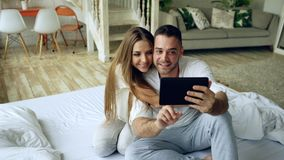 Closeup of Young cute and loving couple having video chat holding smartphone and chatting to friends sitting in bed at. Young cute and loving couple having video royalty free stock photos