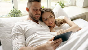 Young cute and loving couple using tablet computer and talking lying in bed in the bedroom at morning stock footage