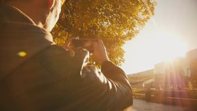 Young cute man taking pictures of the dawn. Slo-mo stock video footage