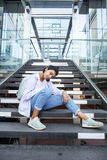 Young cute modern indian girl at university building sitting on stairs reading a book, wearing hipster glasses. Lifestyle people concept close up Stock Image