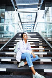 Young cute modern indian girl at university building sitting on stairs reading a book, wearing hipster glasses. Lifestyle people concept close up Stock Photo