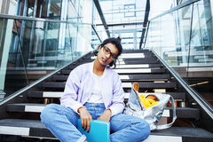 Young cute modern indian girl at university building sitting on. Stairs reading a book, wearing hipster glasses, lifestyle people concept close up Royalty Free Stock Images