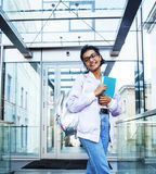 Young cute modern indian girl at university building sitting on. Stairs reading a book, wearing hipster glasses, lifestyle people concept close up Royalty Free Stock Image