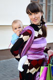 Young cute mother with baby in sling Stock Photos
