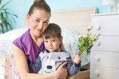 Young cute mother with her little male son dressed in pyjamas, sit together against bedroom interior, have fun. Affectionate lovel. Y mum embraces small kid with Stock Photos