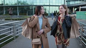 Young cute multiethnic girls with shopping bags. Young attractive multiracial girl friends with shopping bags holding hands walking on pedestrian bridge and stock video footage