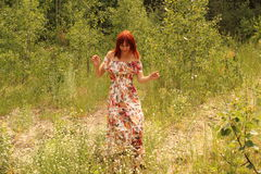 Young cute red hair female at summer forest catching butterflies Royalty Free Stock Photography