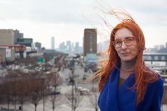 Young cute red-haired woman in a blue coat and glasses standing on the background of the big city, her hair fluttering. In the wind, portrait Royalty Free Stock Images