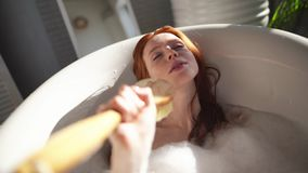 Young cute redhead woman lies in the bathroom with foam and sings stock video