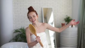 Young cute redhead woman sings in the bathroom, using a brush as a microphone. Cute girl sings with her eyes closed and stock footage