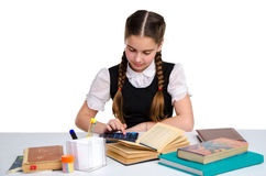 Young cute schoolgirl in unform. Doing homework isolated on white background Royalty Free Stock Image