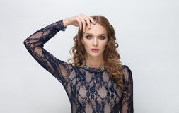Young cute serious blonde teen model in blue dress with curly hairstyle posing on white studio background touching her forehead Royalty Free Stock Images