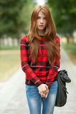 Young cute serious redhead student lady in red plaid jacket with folded hands posing outdoors on park path with blurred green tre Royalty Free Stock Image