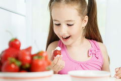 Young cute smiling european little girl is eating ripe jucy strawberry with sour cream and holding white plate of many. Young cute smiling european little girl Royalty Free Stock Images