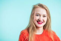 Young cute smiling girl on blue background. Close up portrait, copy space Stock Photo