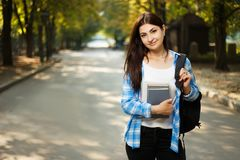 Young cute smiling student woman with backpack and notebooks sta. Nding in park Stock Image