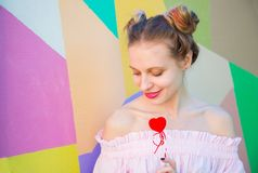 Young cute smiling woman with colorful hair holding red heart in Stock Image