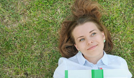 Young cute student with book lying on the grass in the park Stock Photography